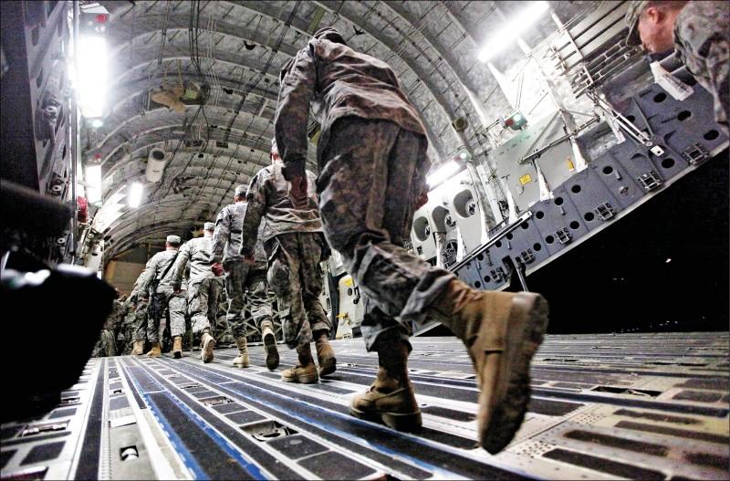 美國國防部宣布,將在明年元月15日前將駐阿富汗美軍從4500人縮減為2500人,駐伊拉克美軍也將由3000人減至2500人。圖為美國陸軍第一騎兵師和澳洲第三旅官兵,2011年12月在伊拉克「伊瑪目阿里空軍基地」,登上即將起飛的C-17「全球霸王III」戰略運輸機。(法新社檔案照)