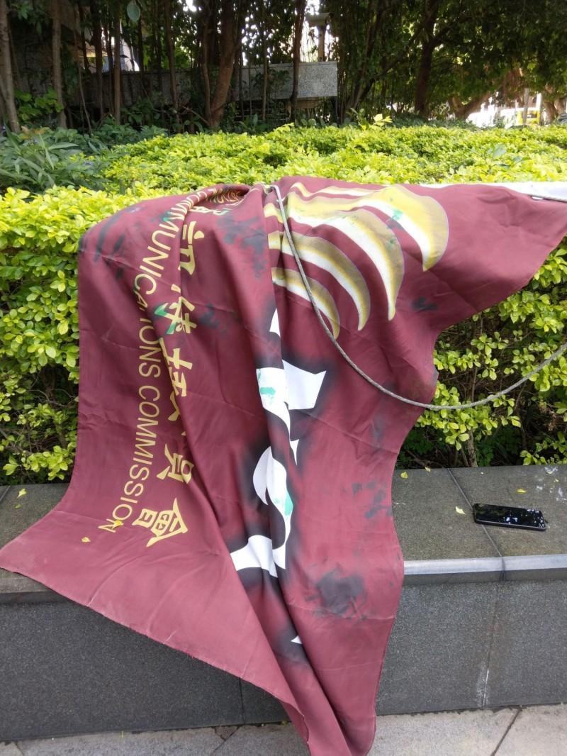 NCC旗幟遭扯下噴漆。(記者王冠仁翻攝)