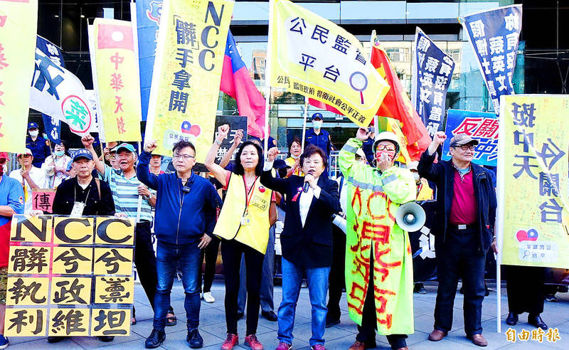 Former Government Information Office director-general Chung Ching, fourth right front in yellow vest, takes part in a rally outside the National Communications Commission in Taipei yesterday to protest the commission's decision to reject CTi News' license renewal application. Photo: Chu Pei-hsiung, Taipei Times