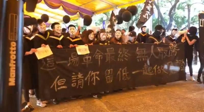 香港中文大學畢業生戴上象徵反抗極權的經典電影《V怪客》,在校內遊行聲援仍被扣押在中國深圳市的12名港人。(圖截自「中大校園電台 CUHK Campus Radio」臉書直播影片)