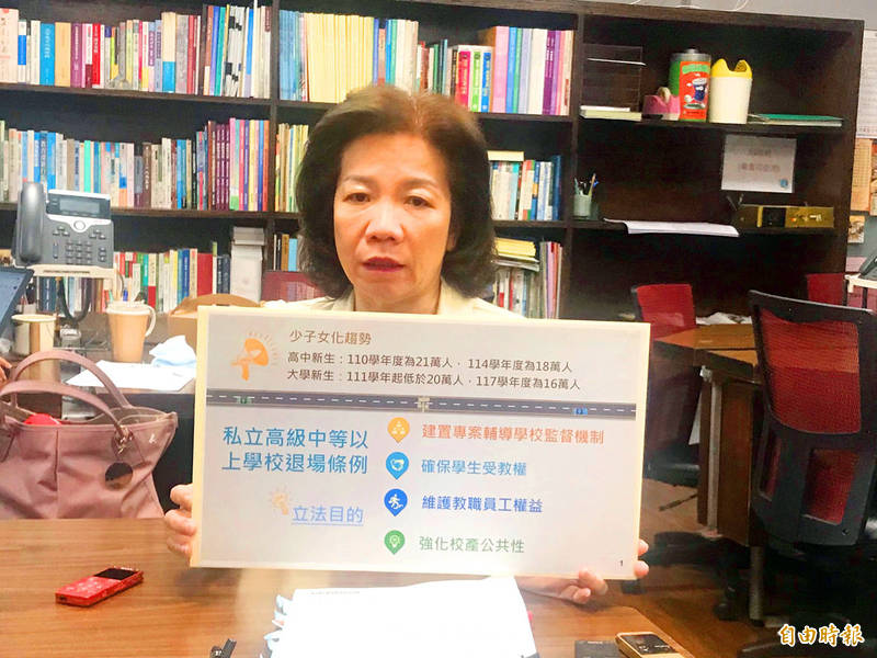 Department of Technological and Vocational Education Director Yang Yu-hui holds up a card showing the conditions that need to be fulfilled as part of a draft bill for disbanding private schools in trouble. Photo: Lin Hsiao-yun, Taipei Times