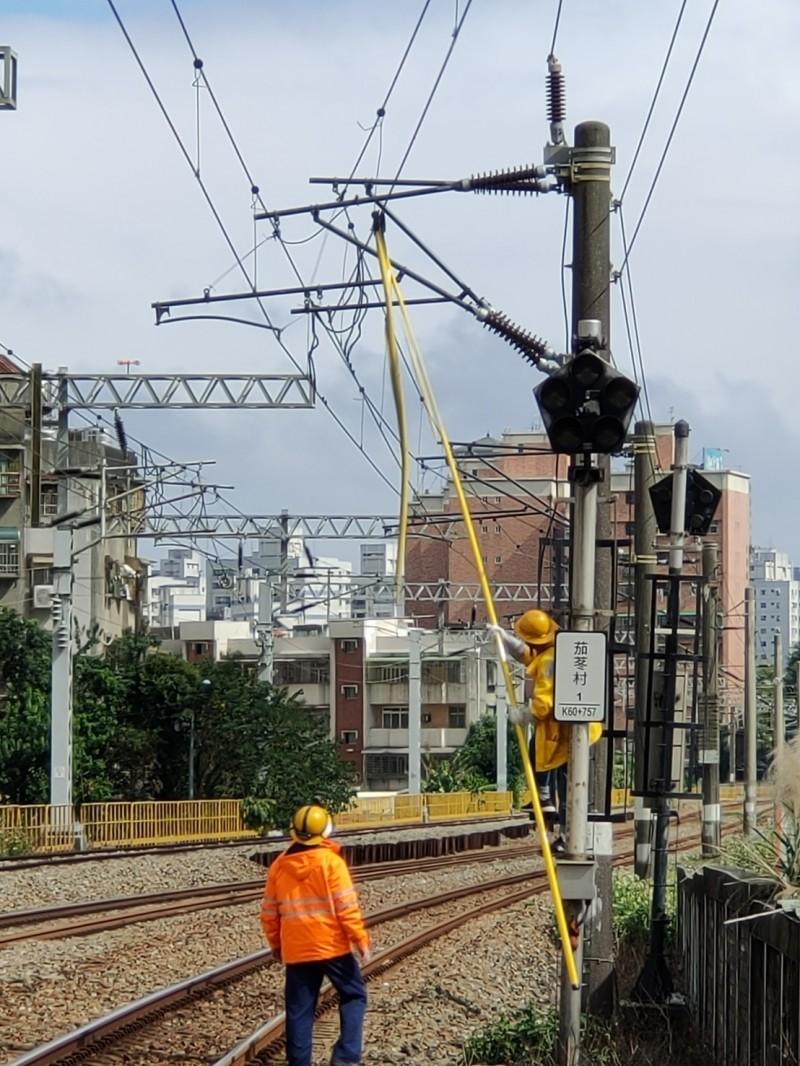 台鐵管理局人員將掛在電車線上的塑膠繩索取下。(記者周敏鴻翻攝)