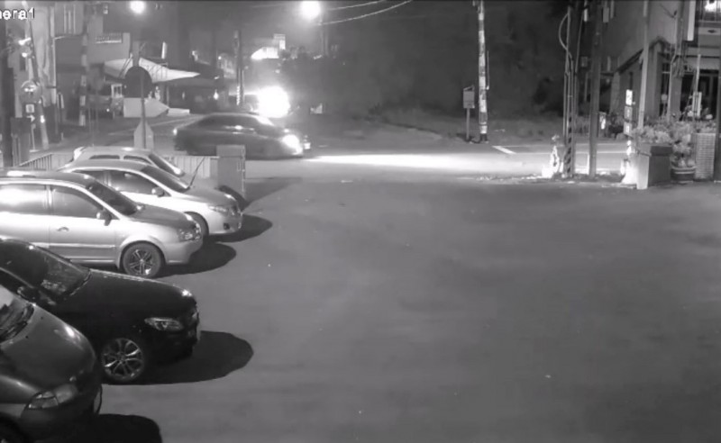 詹男的車子(街道開燈)疑輾壓周男後,過了約20秒,何男的佛祖車(遠處燈光)也開抵又輾壓過周男。(記者楊金城翻攝)