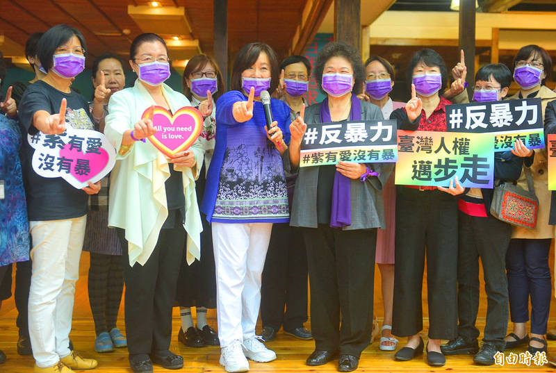 National Human Rights Commission chairwoman and Control Yuan President Chen Chu, front row fourth left, and others yesterday hold signs and wear purple to raise awareness about violence against women at a commemoration ceremony in Taipei. Photo: Chang Chia-ming, Taipei Times
