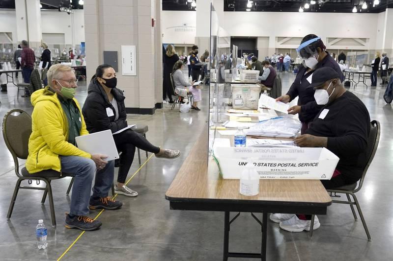 密爾瓦基郡(Milwaukee)的選務人員(右)正在重新驗票,觀察員(左)則隔著透明隔板監督。(美聯社)