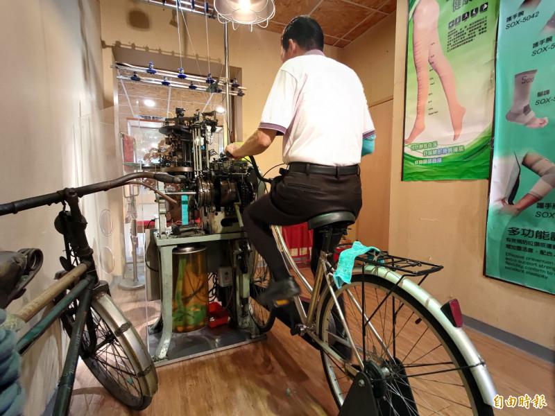 蕭明村(見圖)說,為了讓雙針筒機台「重生」,以腳踏車發電原理改裝織襪機台,只要原地踩踏就可以織出襪子或袖套。(記者陳冠備攝)