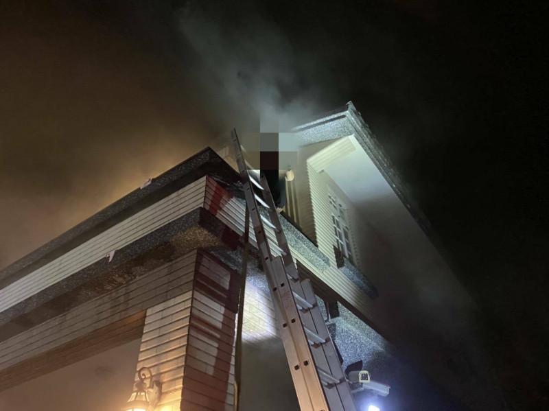 消防人員架梯到2樓救援。(記者江志雄翻攝)