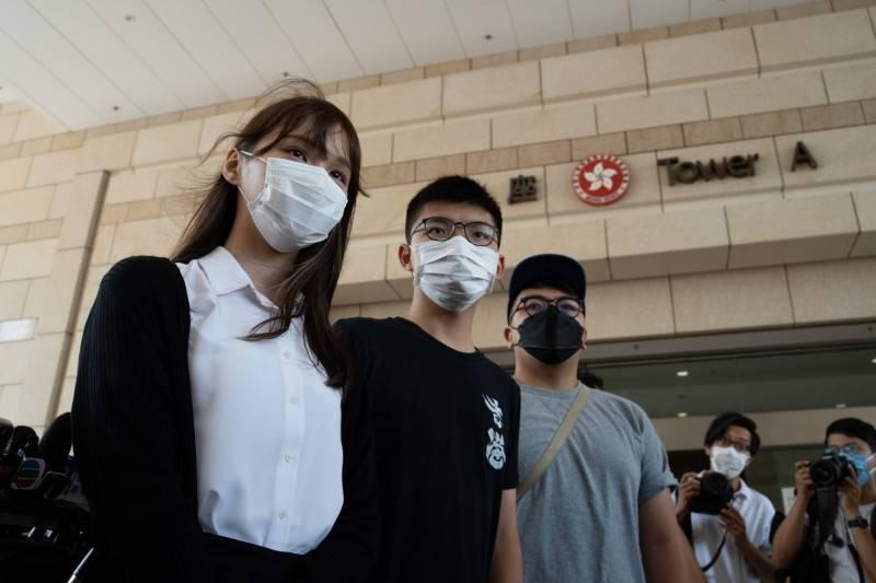 香港眾志前副秘書長周庭(左起)、前秘書長黃之鋒、前主席林朗彥23日將出庭。圖為今年8月5日庭後接受媒體採訪。(彭博資料照)