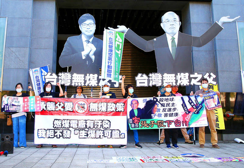 Air Clean Taiwan members yesterday hold up signs and cutouts of Environmental Protection Administration Minister Chang Tzi-chin, left, and Premier Su Tseng-chang during a demonstration outside the agency's headquarters in Taipei. Photo: CNA