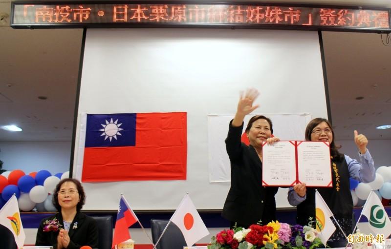 南投縣南投市長宋懷琳(左)及代表會主席張惠卿(右)在視訊中出示與日本栗原市締結姐妹市的盟約。(記者謝介裕攝)
