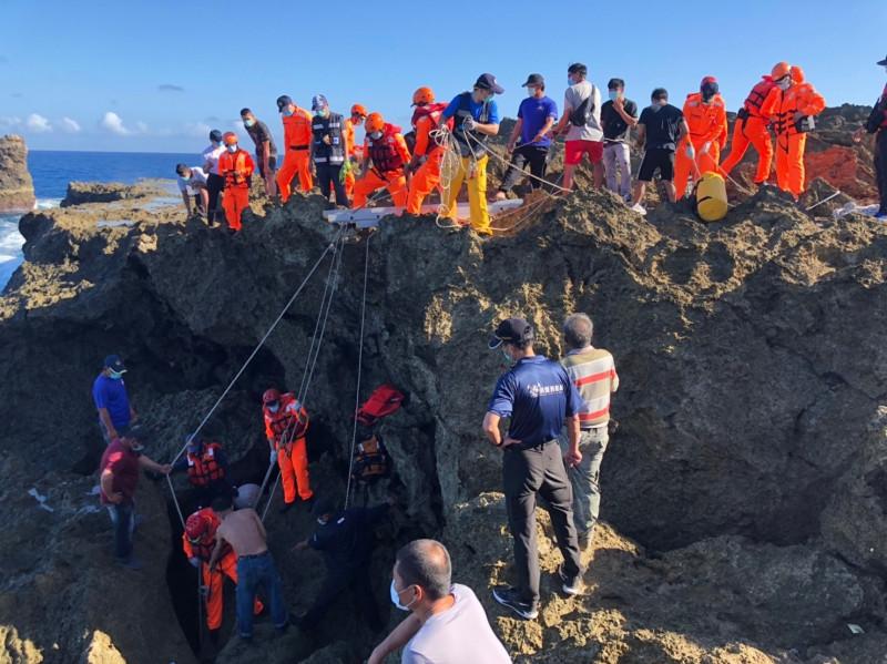 義警消及海巡協力把罹難者拉出礁岩中,助其回家。(記者陳彥廷翻攝)