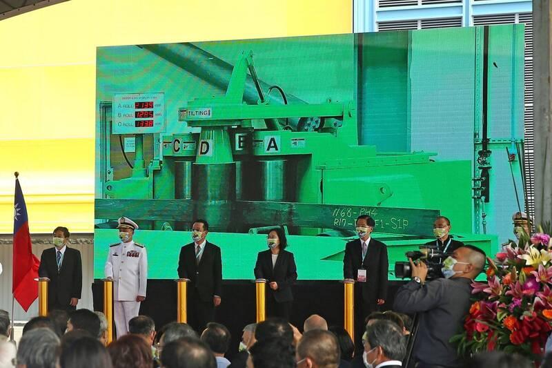 總統蔡英文(左四)24日在台船公司象徵性按鈕啟動潛艦國造,後方投影布幕上首度曝光讓潛艦船身足以抵禦深水水壓的「彎板機」畫面。(中央社)