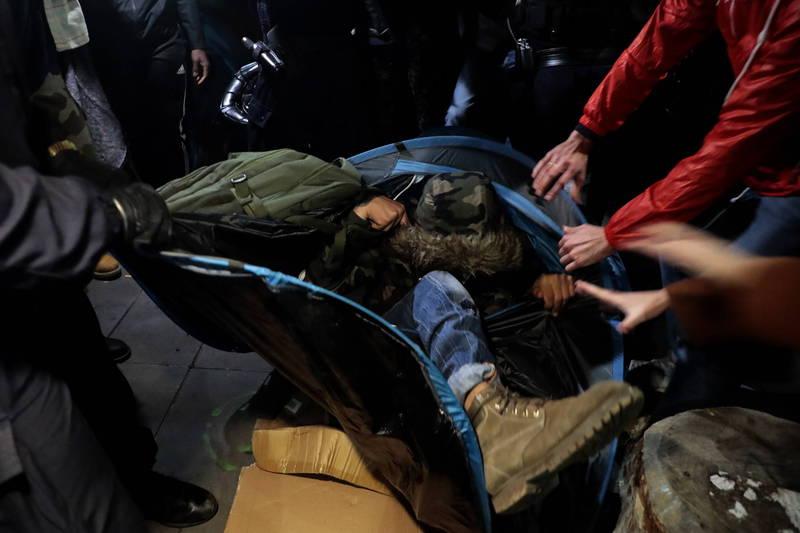 法國巴黎警方強力移除臨時安置難民的帳篷,竟直接動手拉扯搖晃當時尚有難民在內的帳篷。(歐新社)