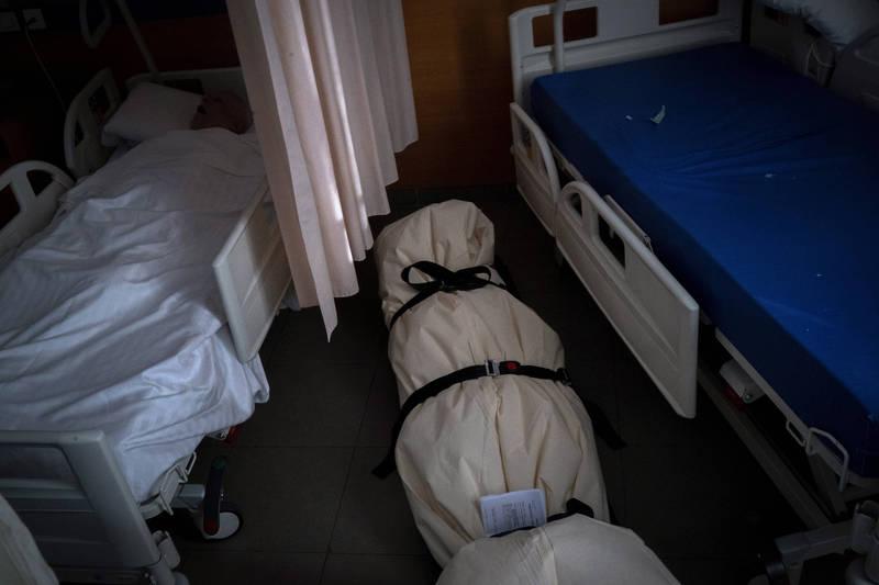 西班牙巴塞隆納某養老院因武漢肺炎死亡的病患,僅能以床單包裹屍體並放置在原處,而一旁(右)還有一名正在熟睡的老人。(美聯社)