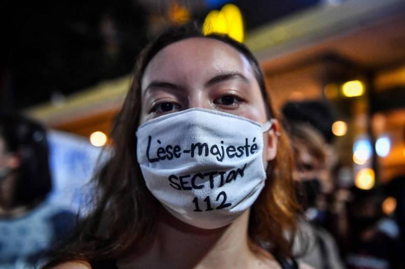 軍政府近日卻祭出《冒犯君主罪》對至少7位示威領袖與人權律師發出傳票,企圖壓下示威活動,示意圖,為一名示威者戴著寫著簡稱刑法112條的《冒犯君主罪》(lese majeste laws)的口罩。(法新社)