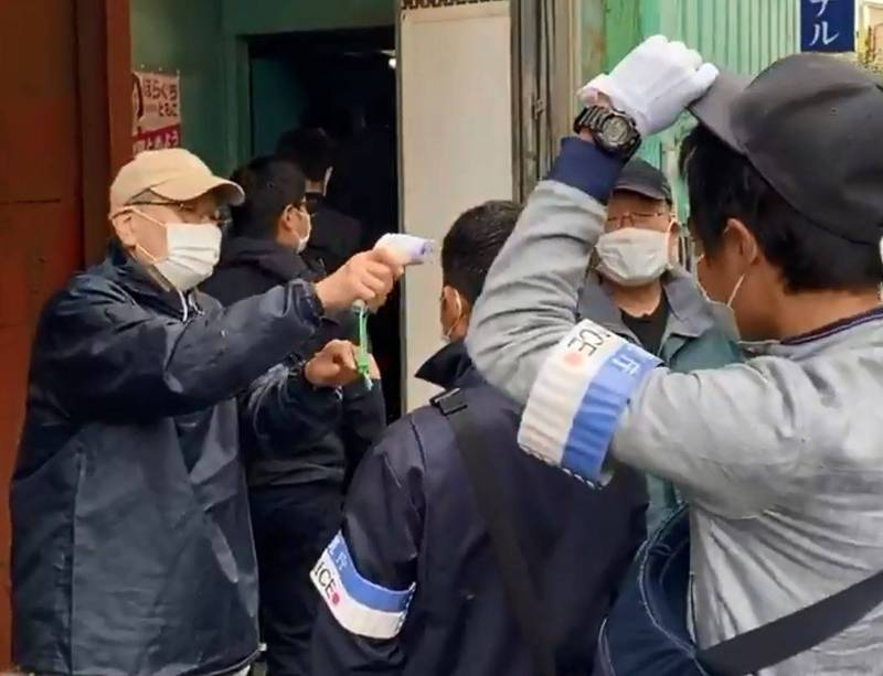 日本警方上個月針對激進左派組織「中核派」時,即使是突襲搜查,但由於疫情,仍乖乖排隊量額溫,當時曾引起熱烈討論。(圖翻攝自推特)