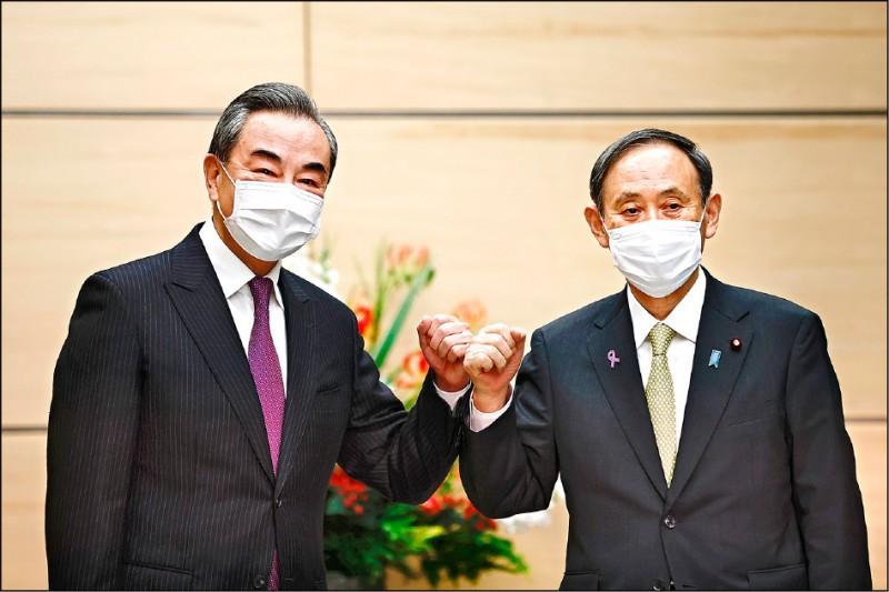 日本首相菅義偉二十五日傍晚接見來訪的中國外交部長王毅。(彭博)