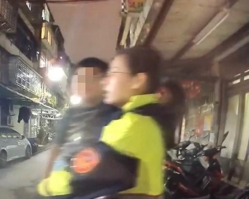 新北警新莊分局丹鳳派出所警花副所長方柏雅(右)抱著走失兩歲男童小強,走了半公里,替她找到回家的路。(記者吳仁捷翻攝)