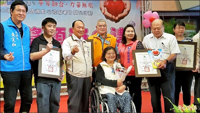 55歲陳月娥(中)因神經失去功能,以輪椅代步,她不被打倒,南安國小將她20多年故事拍成微電影,她與其他得獎者一起合影。(記者游明金攝)