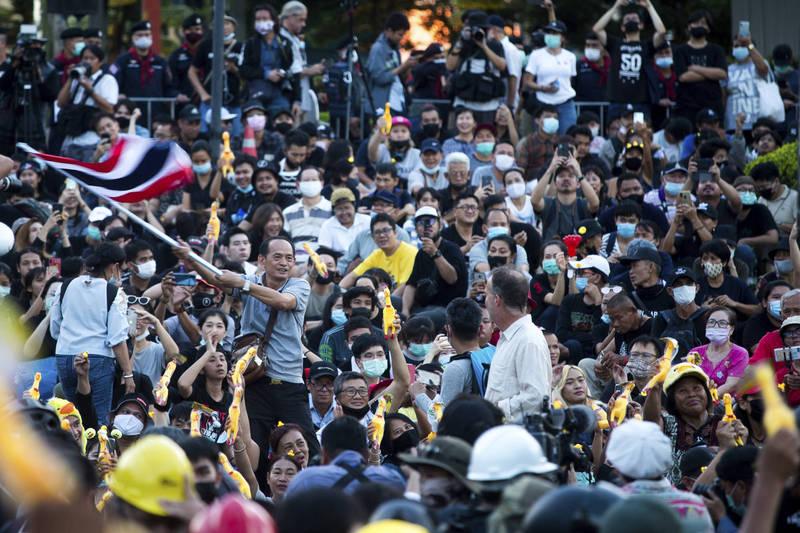 泰國示威者25日聚集在泰國匯商銀行周圍,要求泰王放棄財產控制權、王室資產透明化。(美聯社)