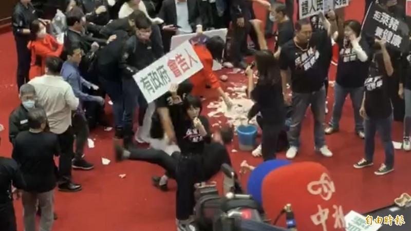 國民黨立委鄭天財彎腰撿塑膠袋,被基進立委陳柏惟抓起來摔飛。(記者陳昀攝)