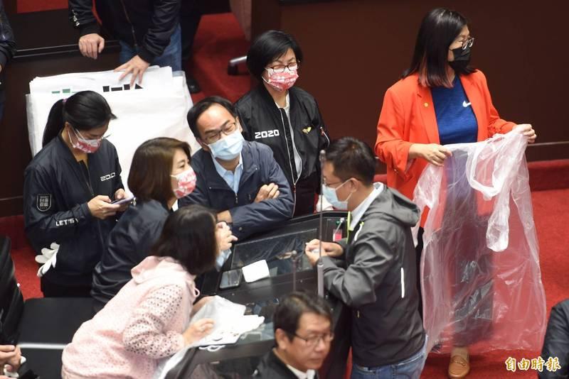 立法院朝野衝突,民進黨立委穿上雨衣備戰。(記者劉信德攝)
