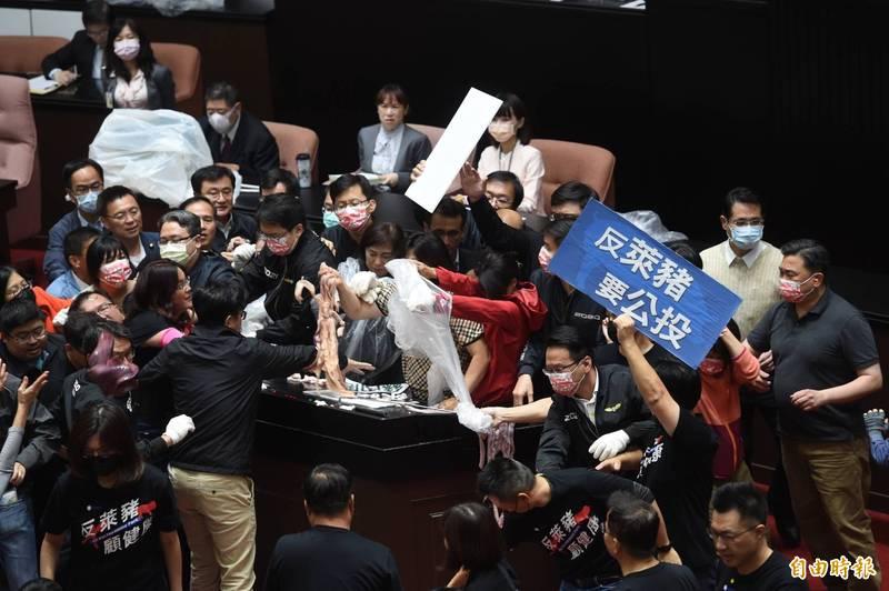 蘇貞昌10時20分一上發言台,國民黨團立即拿豬內臟、豬皮潑在發言台上。(記者方賓照攝)