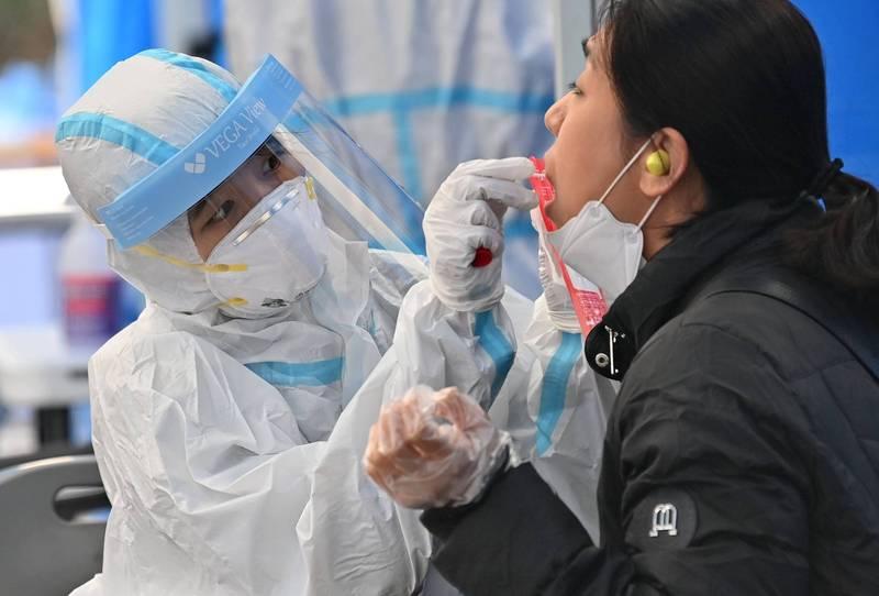 南韓26日新增確診病例569例,單日新增確診連續2日維持在500例以上。圖為南韓醫護人員對民眾採樣篩檢情況。(法新社)