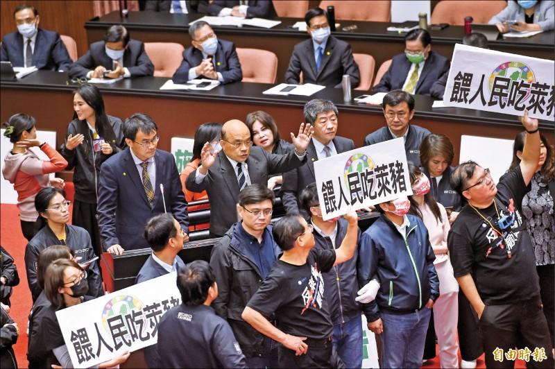 行政院長蘇貞昌昨在大批民進黨立委保護下站上發言台,手持麥克風完成施政報告。 (記者劉信德攝)