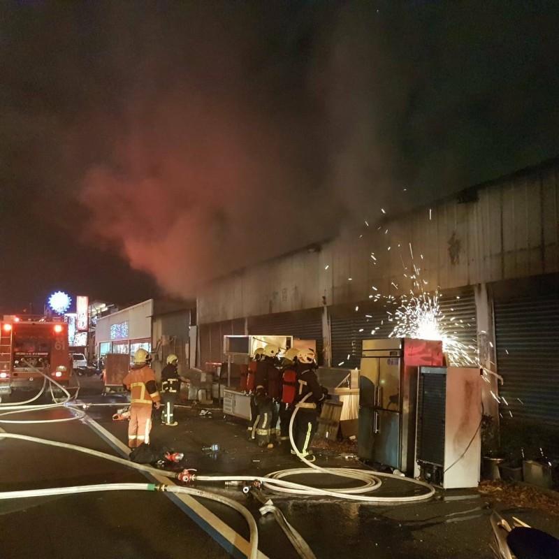 彰化市金馬路一間五金工廠今晚傳出火警,31名消防員與20輛消防車趕往搶救,以切割機破壞鐵捲門後灌救。(記者湯世名翻攝)