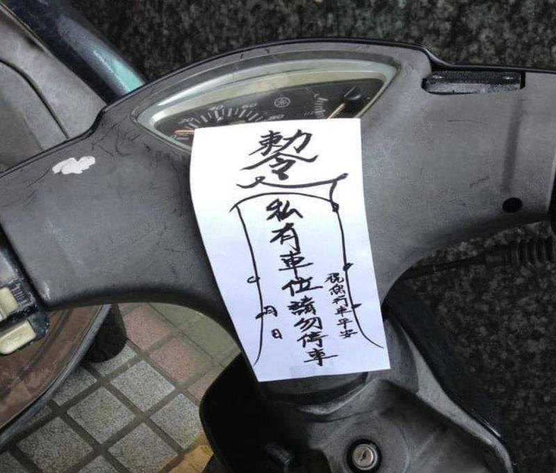 有頻頻被外面的車占用車位而不堪其擾的公司員工出奇招,在亂停車的機車上貼上寫有「敕令」的符咒。(民眾授權提供)