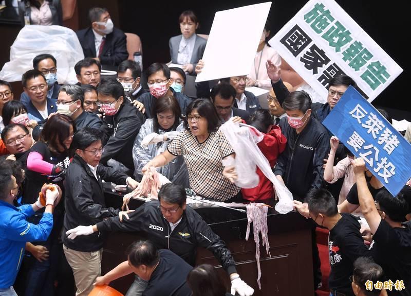 立法院27日舉行院會,藍營立委杯葛後,行政院長蘇貞昌在綠營立委護航下,上台報告並備質詢,國民黨團丟豬隻內臟表達訴求。(記者方賓照攝)