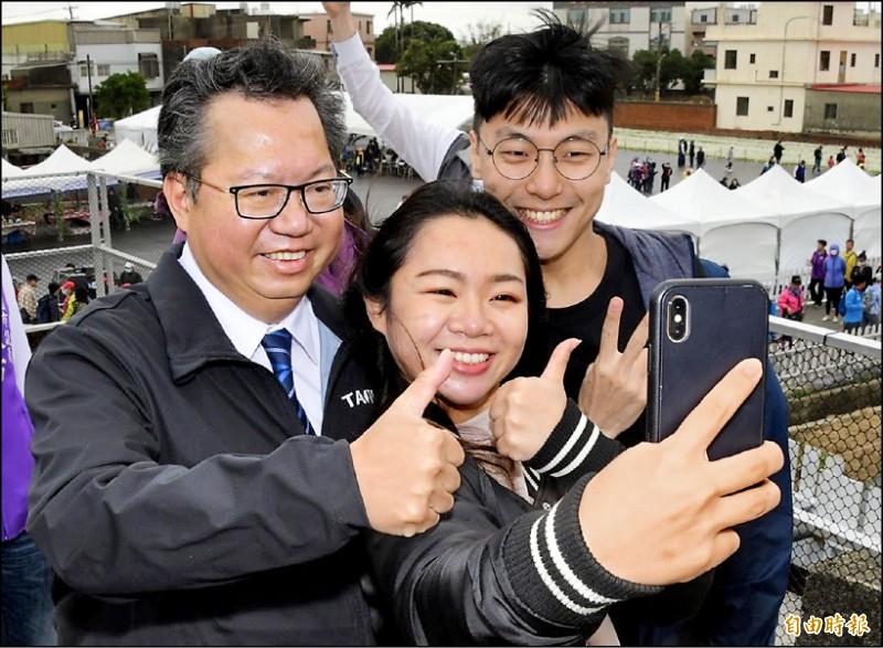 民眾與桃園市長鄭文燦(左)在仙草花節巧遇,開心自拍打卡。(記者許倬勛攝)