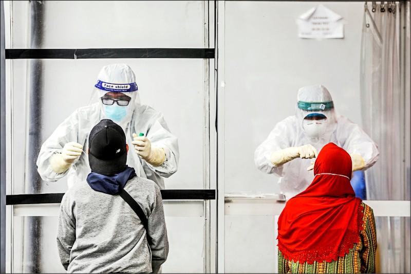 印尼疫情嚴峻,確診病例已破五十萬大關,圖為全副武裝的醫護人員為民眾採檢。(歐新社)