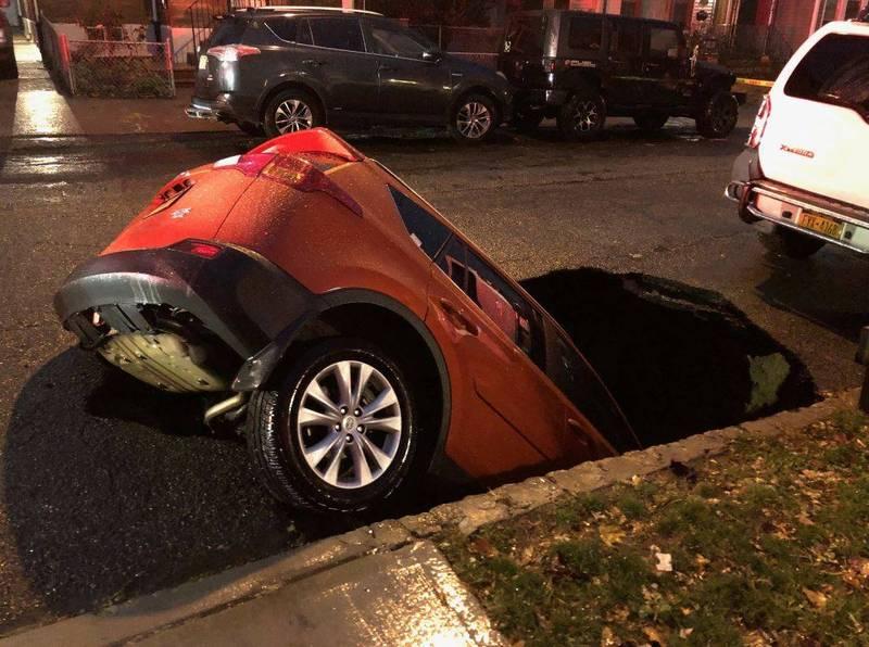 美國紐約皇后區出現天坑,馬路彷彿正在慢慢吃掉車輛。(圖擷自Robert Holden推特)