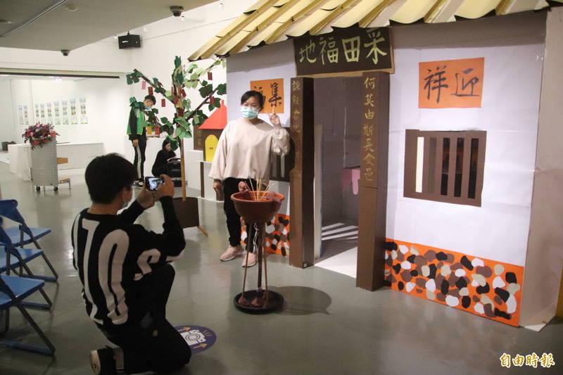 新竹縣縣定古蹟「采田福地」在明新科大藝文中心被縮小20倍,復刻成為裝置藝術,香爐前方還設有最佳攝影點,提供參觀者最佳拍照打卡角度的建議。(記者黃美珠攝)