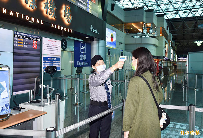 An airport employee takes the temperature of an arriving passenger at Taiwan Taoyuan International Airport yesterday, as the airport complied with more stringent measures issued by the Central Epidemic Command Center. Photo: Hsiao Yu-hsin, Taipei Times