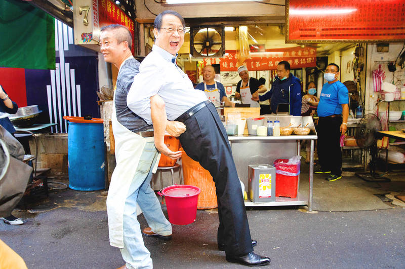 Japanese Representative Hiroyasu Izumi, right, and a beef noodle vendor in Taipei yesterday replicate one of the bilateral friendship symbols unveiled by the Japan-Taiwan Exchange Association. Photo: CNA