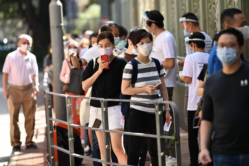 香港第四波疫情持續延燒,港府決定,明天起將實施更嚴格的防疫措施。圖為香港民眾在一處武漢肺炎檢測中心外大排長龍。(法新社資料照)