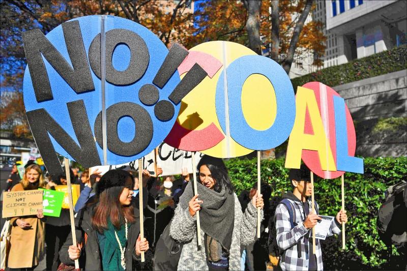 去年11月29日民眾拿著「不要煤炭」標語牌在東京遊行,呼籲採取行動對抗氣候變遷。(法新社)