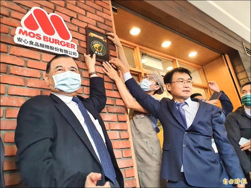 全國第一張台灣豬證明標章!農委會主委陳吉仲(右)昨到台灣摩斯漢堡創始店頒發標章,並和東元集團會長、摩斯董事黃茂雄(左)一起懸掛。(記者簡惠茹攝)