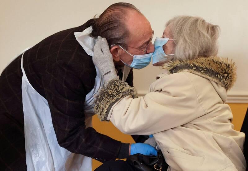 世界衛生組織(WHO )今天公布疫情期間使用口罩的更新版指南中建議,如果與其他人共處一室而室內通風欠佳,則應配戴口罩。圖為英國倫敦一對八十多歲的老夫妻戴著口罩親吻。(路透)