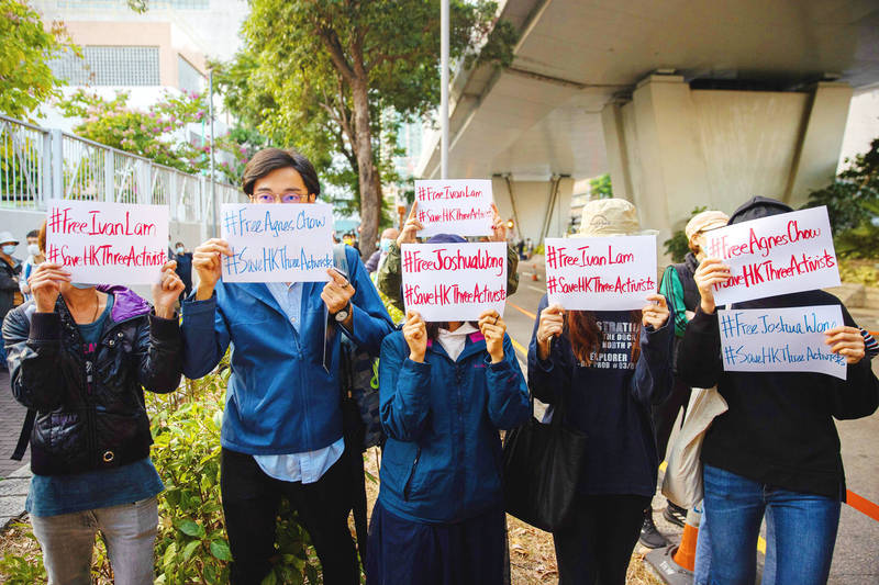 Supporters of democracy advocates Joshua Wong, Agnes Chow and Ivan Lam hold signs outside the West Kowloon Court in Hong Kong yesterday. Photo: EPA-EFE