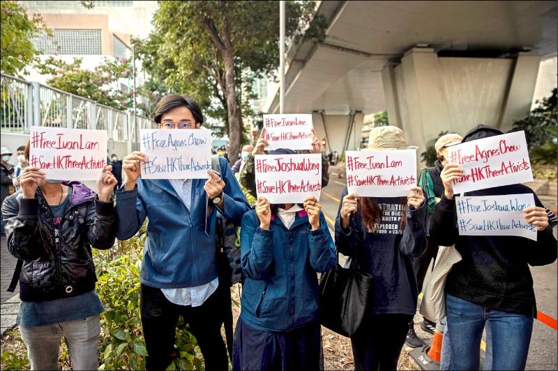 前「香港眾志」成員黃之鋒、周庭和林朗彥二日出庭時,法院外支持者舉標語牌聲援。 (歐新社)