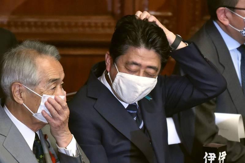 日本前首相安倍晉三(中)甫卸任就捲入招待會弊案,其擔任首相期間的公設第一秘書因涉及不當使用政治獻金,被東京檢調正式以《政治資金規正法》的隱瞞使用資金的罪嫌立案調查。(法新社)