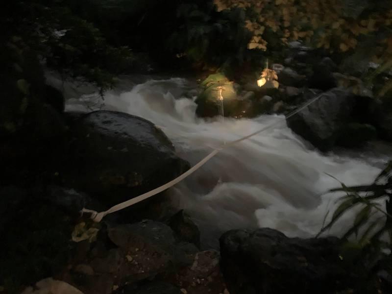1名婦人在陽明山國家公園野溪泡湯遭暴漲溪水沖走,新北消防隊員正設法在下游架設攔截繩索渡溪救援。(記者林嘉東翻攝)