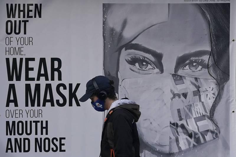 11月21日舊金山一名路人經過一面呼籲戴口罩的街頭塗鴉。(美聯社)