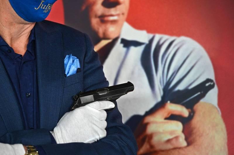 初代007的半自動華瑟PP手槍以25萬6千美元被影迷標走。圖為拍賣公司高層示範初代007電影海報持槍姿勢。(法新社)