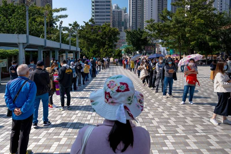 香港疫情持續發燒,圖為香港民眾排隊等待採檢的畫面。(彭博)