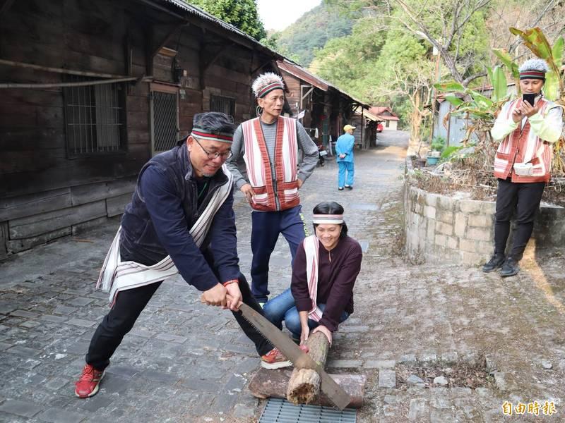 「泰好玩獵人體驗營」提供遊客鋸木體驗,後方為松鶴部落於日據時期伐木遺留下來的檜木屋。(記者歐素美攝)